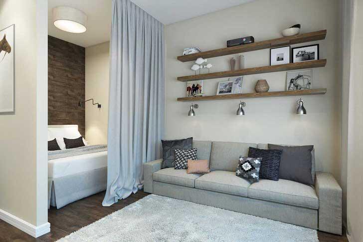 Дизайнерская планировка квартиры-студии размером 40 квадратных метров делит пространство на гостиную и спальню. Место для отдыха завешено плотной тяжелой шторой.