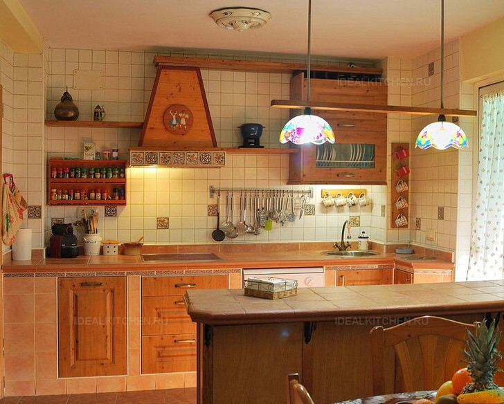 Кухня в средиземноморском стиле с правильно подобранным освещением. Потолочные люстры с витражными плафонами делают свет мягким.