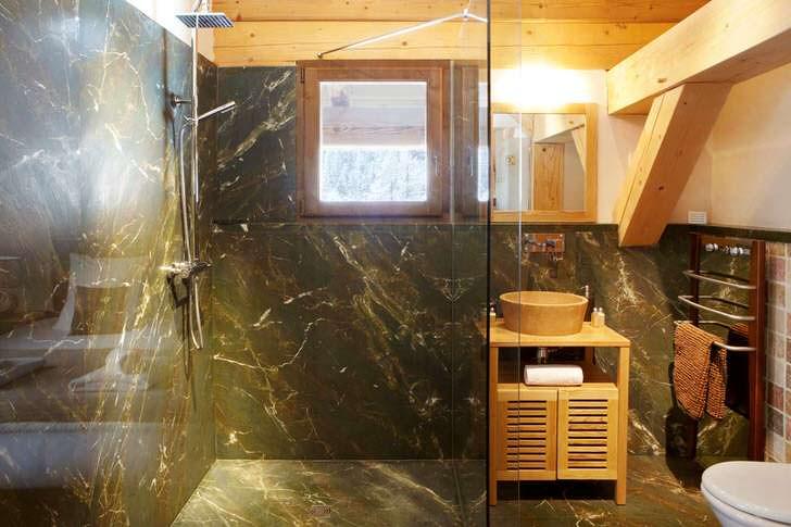 Ванная комната с душевой кабиной в стиле шале отделана плиткой, имитирующей мрамор. Элегантное и практичное оформление для интерьера загородного дома.