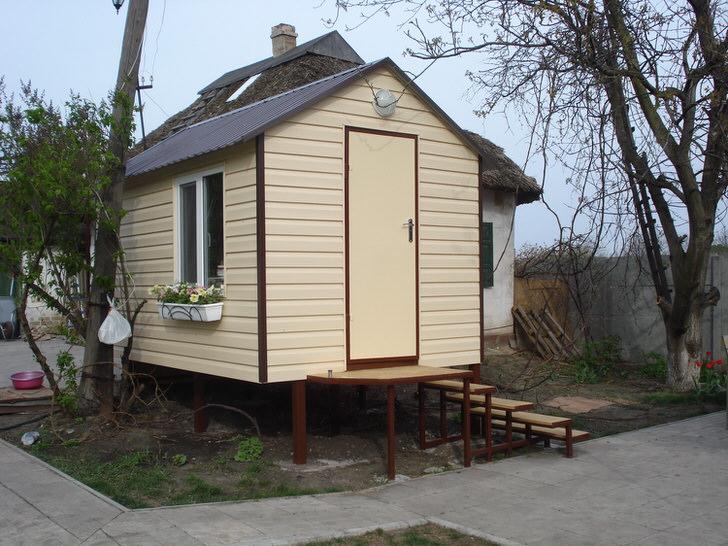 Дачный домик на сваях обшит сайдингом. Отделка фасада бежевого цвета привлекательно смотрится в общей композиции двора.