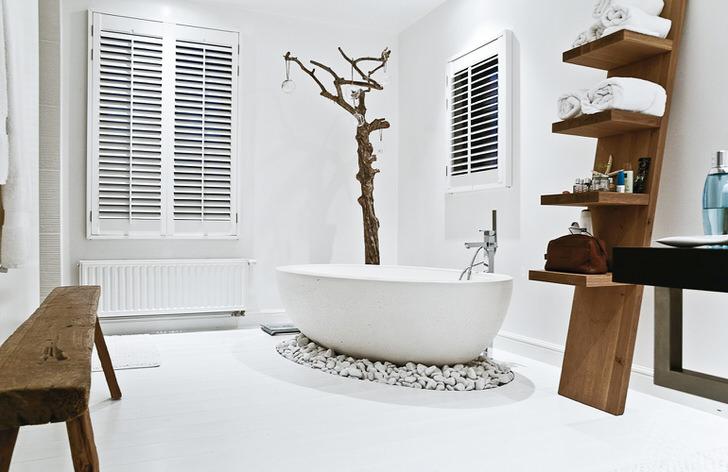 Правильно составленный проект дизайна ванной комнаты в скандинавском стиле. Ванна стоит на искусственной возвышенности из камня. В качестве вешалки используется ветка дерева, покрытая специальным лаком.