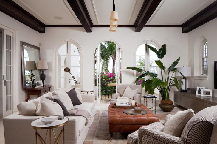 Комната для гостей оформлена в средиземноморском стиле. Изящным украшением интерьера становится большое, раскидистое зеленое растение, высаженное в керамический горшок.