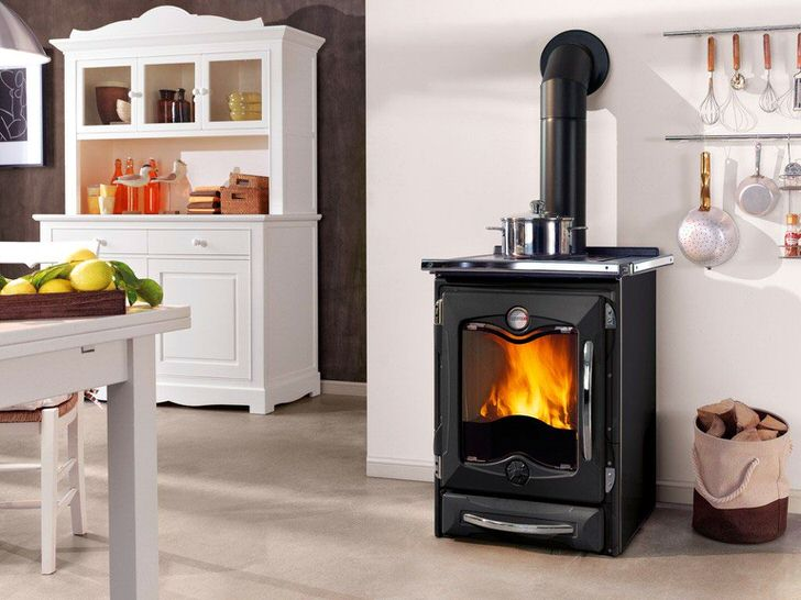 Печь-камин длительного горения в чугунном корпусе будет отлично смотреться в интерьере дачной кухни. Особенно, если он оформлен в стиле кантри.