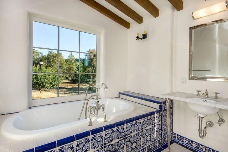 Белоснежная ванна обшита ярко-синей плиткой с белым узором. Правильно подобранная керамическая плитка и деревянная отделка потолка делают интерьер легким и стильным.