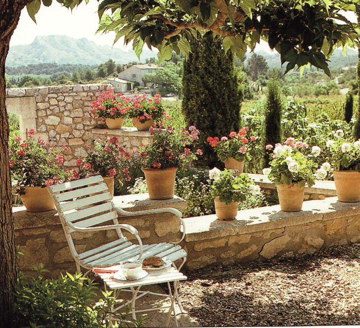 Керамические горшки с цветами используются для украшения двора в средиземноморском стиле.