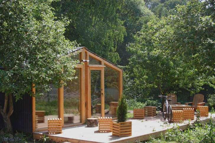 Стильный модульный дом для оформления дачного участка был изготовлен из дерева. Главной особенностью строения становятся панорамные окна.