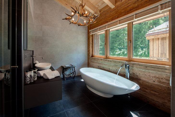 Ванная комната в стиле шале на мансардном этаже, как пример правильно подобранного освещения. Потолочная люстра, имитирующая рога лося, дает мягкий, теплый свет.