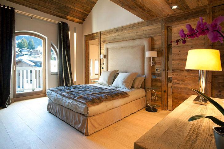 Отделка стен и потолка из дерева, большие окна, приглушенный свет - все, что нужно для организации интерьера спальни в стиле шале.