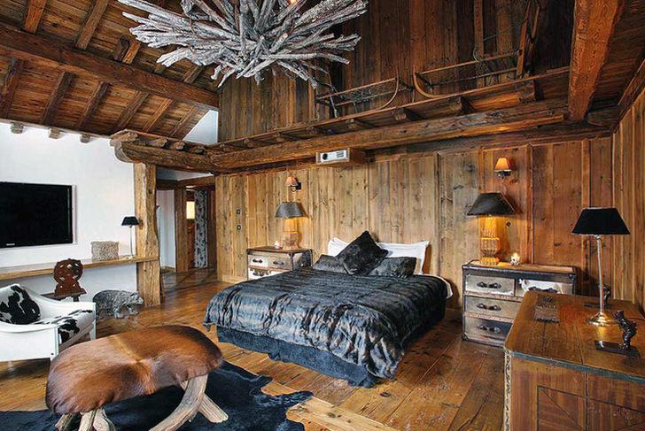 Спальня в стиле шале в темных тонах в охотничьем домике на юге Германии. В комнате царит непередаваемая романтическая атмосфера.