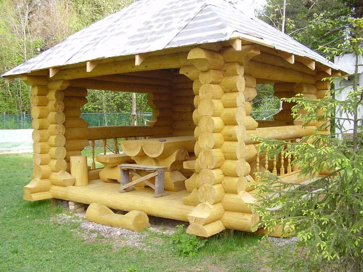 Беседка в стиле шале обставлена креативной мебелью из деревянного сруба.