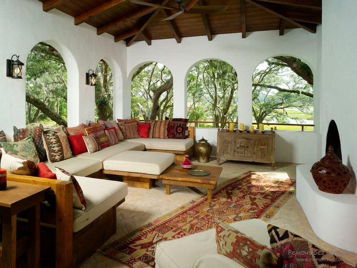 Веранда загородного дома оформлена в соответствии со средиземноморским стилем. Интересной особенностью становится декор большим количеством разноцветных подушек.