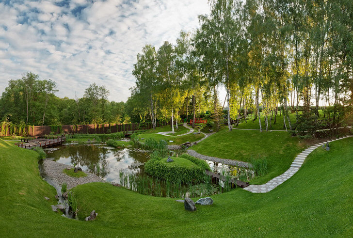 Искусственный пруд за домом, который оформлен в стиле шале. Необычное, смелое решение для проектировки ландшафтного дизайна.