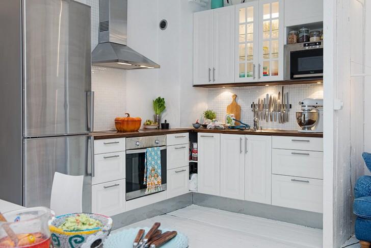 Роскошная кухня в скандинавском стиле с правильно подобранной мебелью и встроенной техникой в небольшой квартире в Киеве.