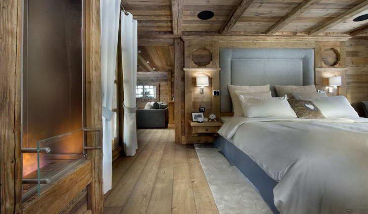 Для спальни в стиле шале подобрана деревянная мебель. В центре композиции стоит кровать с мягким высоким изголовьем.