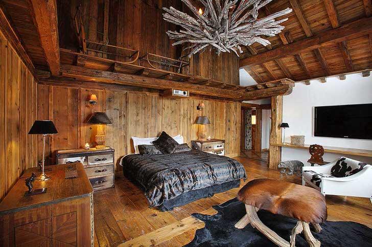Эффектное оформление спальни в стиле шале примечательно правильно подобранными деталями. Темная цветовая гамма разбавлена светлыми элементами интерьера.