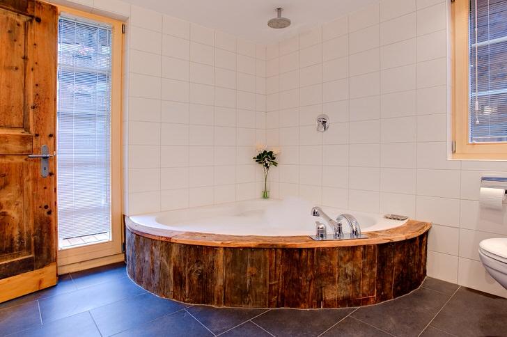 Для организации интерьера использовалась угловая ванная. В соответствии стилю она была закрыты панелью из натурального дерева.