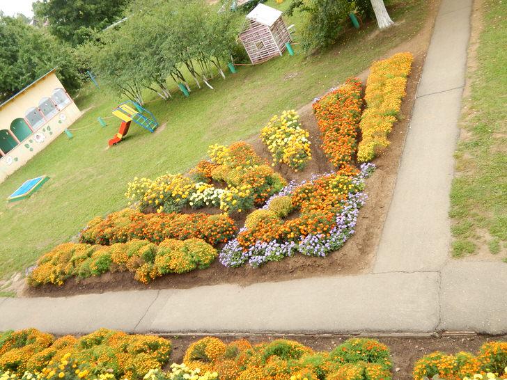 Модульный цветник в форме лучистого солнца гармонично смотрится на детской площадке.