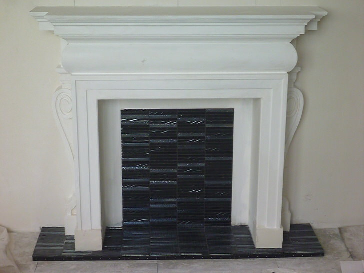 Камин оформлен с использованием лепнины из бетона, выкрашенной в белый цвет.