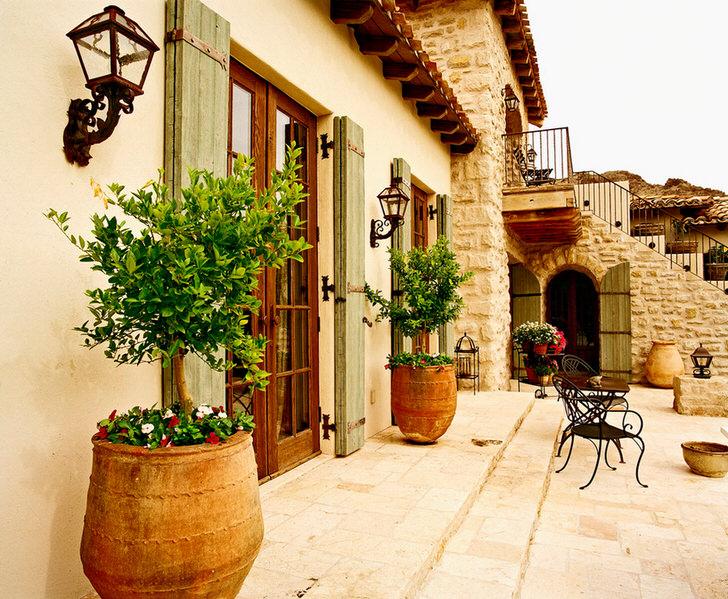 Внутренний дворик в средиземноморском стиле украшают горшки с живыми растениями. Привлекательный дизайн, мебель с витиеватыми спинками, керамические горшки создают уютную, расслабляющую атмосферу.