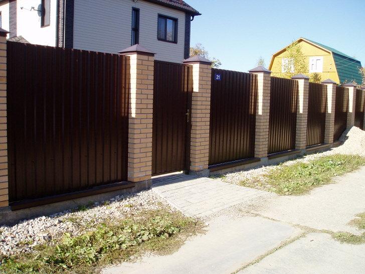 Модульный забор темно-коричневого цвета с отделкой из кирпича - классика жанра, если говорить об оформлении загородных участков.