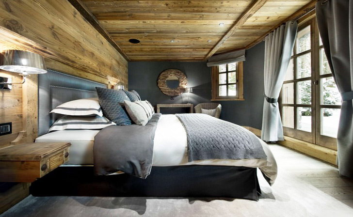 Мягкая большая кровать в спальне в стиле шале напоминает пуховую перину.