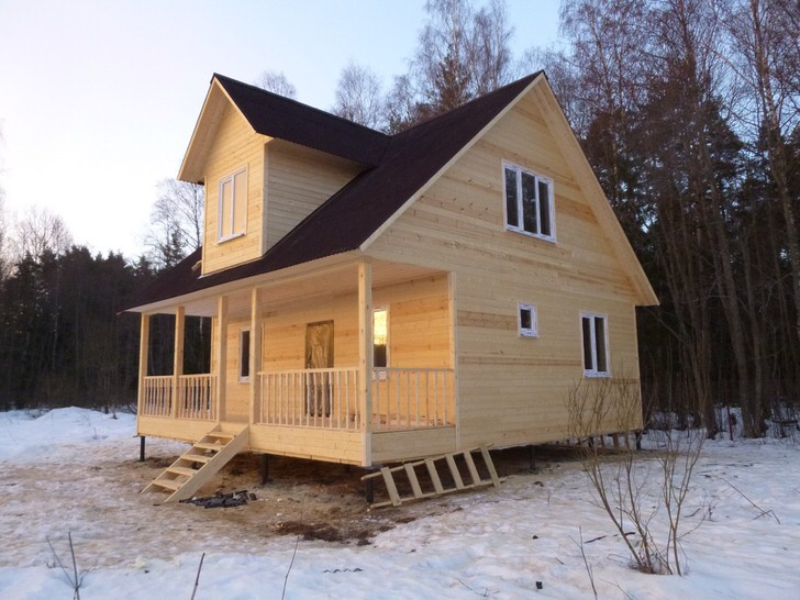 Деревянный дом 6 на 8 метров с мансардой и кукушкой. Возникают сомнения в необходимости большой терассы. Для дружных вечерних посиделок из оставшегося от дома материала можно сделать беседку.