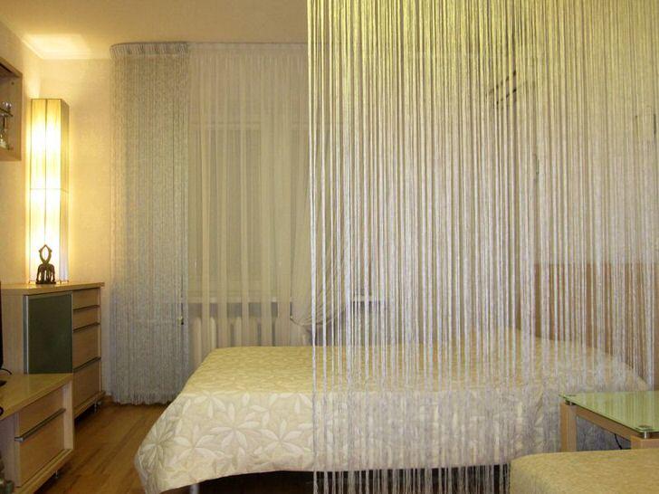 Изысканно и романтично можно оформить интерьер просторной спальни отгородив спальное место шторой из светлых нитей.
