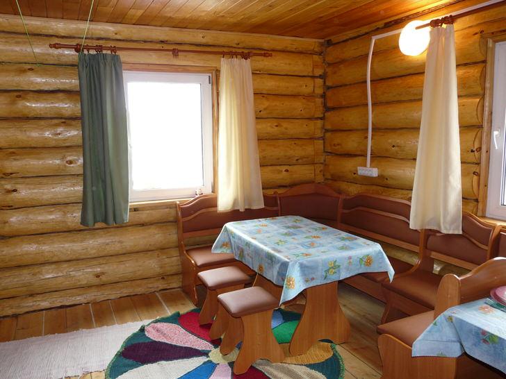 Просторная комната отдыха в доме с баней. За таким столом может разместиться большая компания или дружная семья, а на ночь теплая комната может превратиться в спальню для гостей.