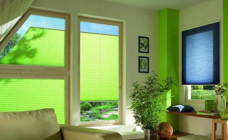 Полупрозрачные шторы плиссе салатового цвета гармонично встраиваются в комнату на мансардном этаже загородного дома.