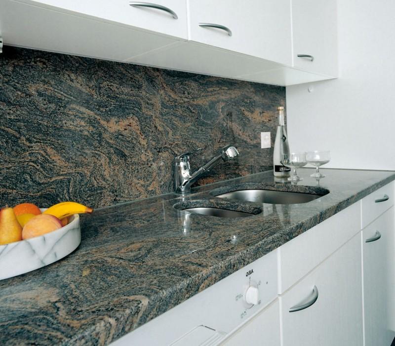 Длинная столешница из акрилового искусственного камня под мрамор. Белый цвет кухонного гарнитура и стен удачно гармонирует с палитрой столешницы и ниши.